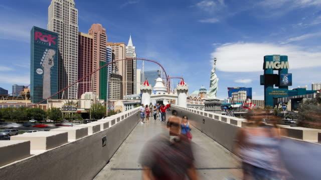 tourists cross a footbridge over las vegas boulevard. - the strip las vegas stock videos & royalty-free footage