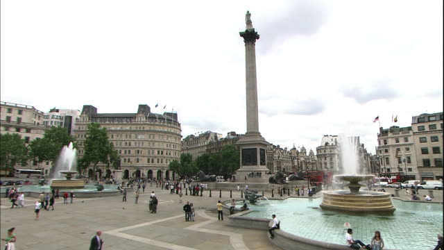 Tourists cross Trafalgar Square near a fountain.