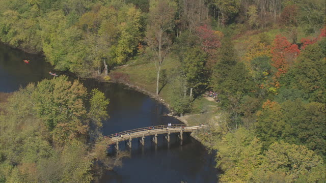 aerial tourists crossing old north bridge, with autumn trees on both sides / massachusetts, united states - american revolution stock videos & royalty-free footage