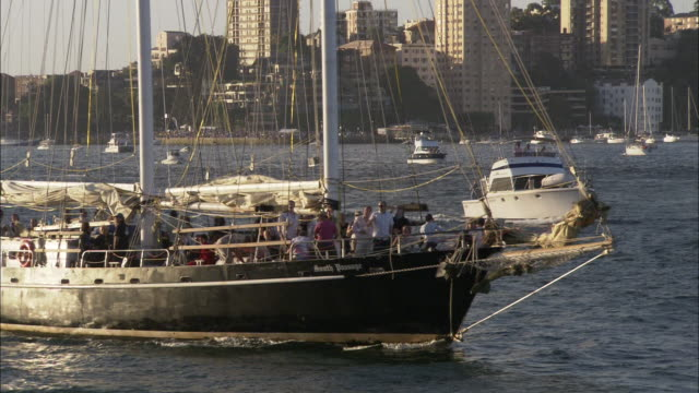Tourists cruise across Sydney Harbor on tour boats.