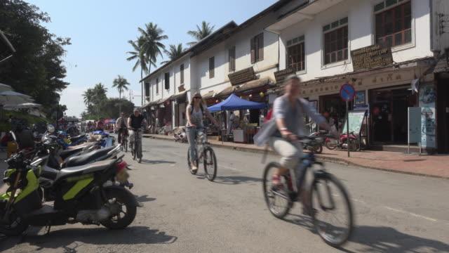 vídeos y material grabado en eventos de stock de tourists cycling in main street - señal de nombre de calle