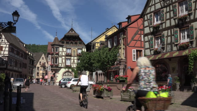 vidéos et rushes de tourists cycling in old town of kaysersberg - village