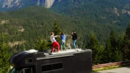 Tourists dancing on edge of cliff with breathtaking view