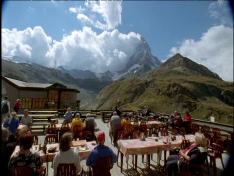 tourists dash about as cloud billows over matterhorn switzerland - switzerland stock videos and b-roll footage