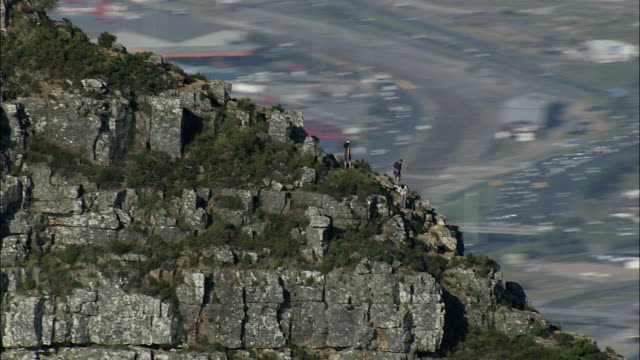 aerial zi tourists descending lion's head, cityscape in background, cape town, western cape, south africa - ライオンズヘッド点の映像素材/bロール