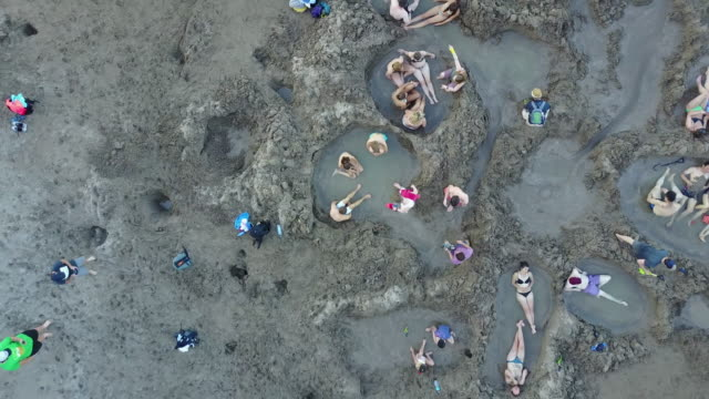 tourists dig holes in the sand to find hot water geothermal springs that rise from below. - 健康スパ点の映像素材/bロール
