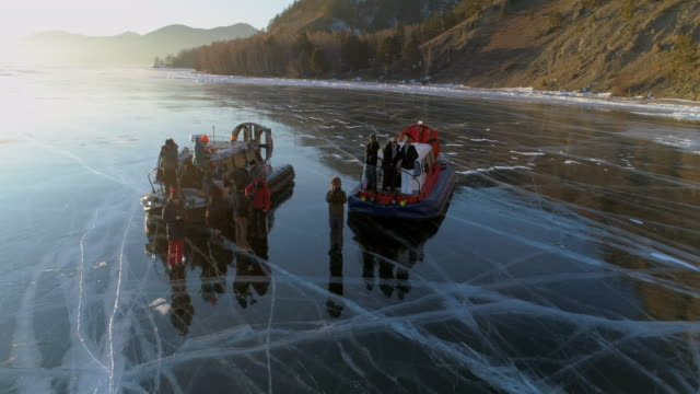 tourists disembarking from hovercraft over frozen lake baikal against bright sky - tourist stock-videos und b-roll-filmmaterial