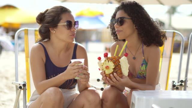 vídeos de stock, filmes e b-roll de turistas que bebem o suco de abacaxi na praia tropical - drink
