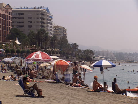 Tourists enjoy a beach in Costa Del Sol Spain.
