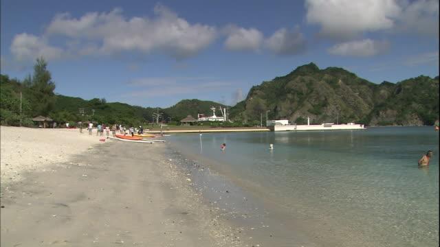 Tourists enjoy a sandy beach on Chichijima Island.