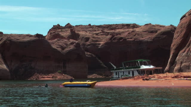 tourists enjoy lake powell near towering rock formations. - lake powell stock videos and b-roll footage