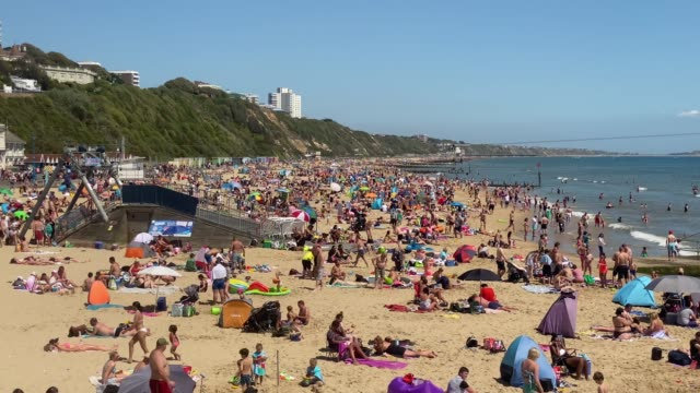 tourists enjoy the hot weather at bournemouth beach on may 25 2020 in bournemouth united kingdom the british government has started easing the... - beach stock videos & royalty-free footage