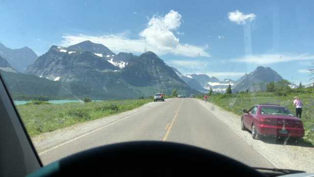 tourists enjoy the view at us glacier national park - glacier national park us stock videos and b-roll footage