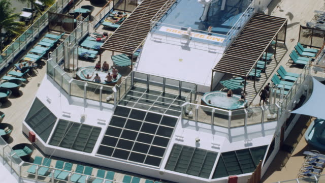 ws aerial pov tourists enjoying near swimming pool in cruise ship / charlotte amalie, st. thomas - virgin islands, united states - ponte di una nave video stock e b–roll