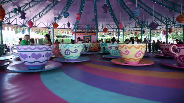 ms tourists enjoying teacup ride in amusement park / hong kong - tea cup stock videos & royalty-free footage