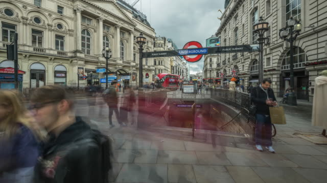 tourists enjoying the sights and a little sunshine move rapidly around and into the underground entrance to piccadilly circus tube station - entrance sign stock videos & royalty-free footage
