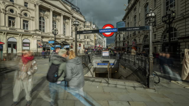 tourists enjoying the sights and a little sunshine move rapidly around and into the underground entrance to piccadilly circus tube station as the frame slowly zooms out - entrance sign stock videos & royalty-free footage