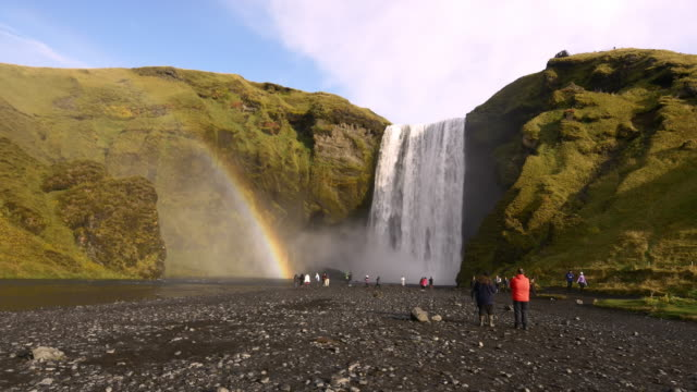 Tourists enjoying the view of Skogafoss waterfall in Iceland