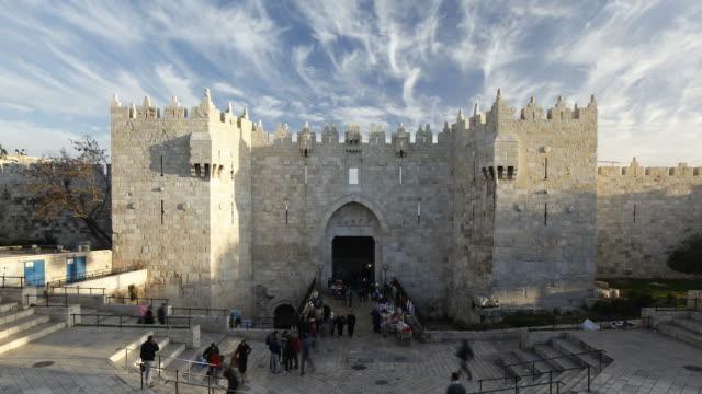 vídeos de stock, filmes e b-roll de tourists enter and exit the old city damascus gate in jerusalem, israel. - jerusalém