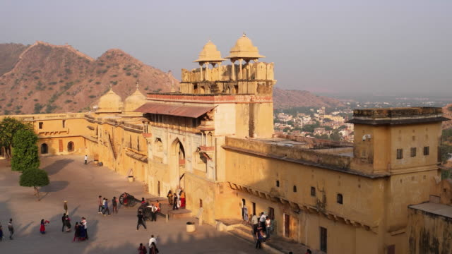 tourists entering the amber fort through the main entrance gateway of the royal rajasthani palace, a unesco world heritage site - fortress stock videos and b-roll footage
