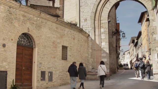 zo tourists entering through archway into assisi, italy - ウンブリア州点の映像素材/bロール