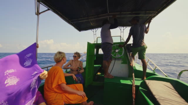 tourists, european women, are resting in the shade under the tent and talking with a local guide and the captain aboard a fishing boat during the deep sea fishing trip in the indian ocean, at the sri lanka coast. - sri lanka people stock videos & royalty-free footage