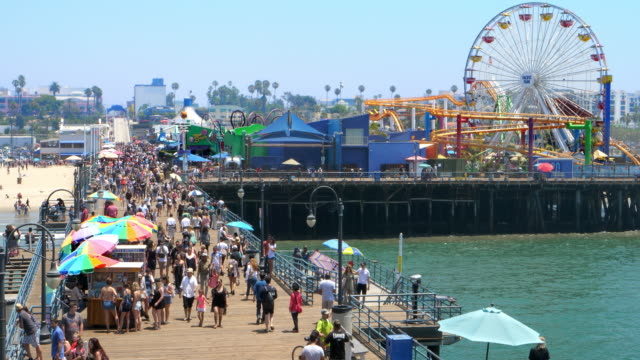 Tourists explore Santa Monica Pier landmark Rollercoaster and famous Ferris wheel in Los Angeles, California, 4K