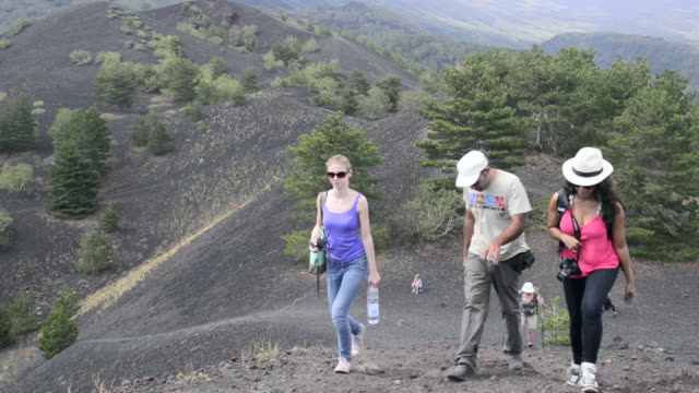 Tourists exploring an old lava flow from an eruption of Mount Etna Volcano, Sicily, UNESCO World Heritage Site, Italy, Europe