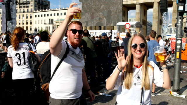 tourists from the united states celebrate on the fan mile at the brandenburg gate despite the historic defeat of the german national football team... - united states national team stock videos & royalty-free footage