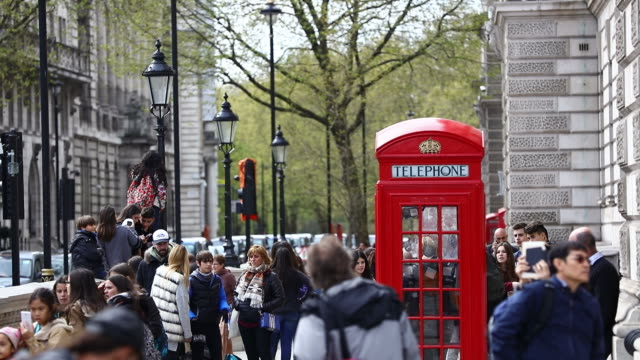 tourists gather around a traditional red phone box in london - telephone booth stock videos & royalty-free footage