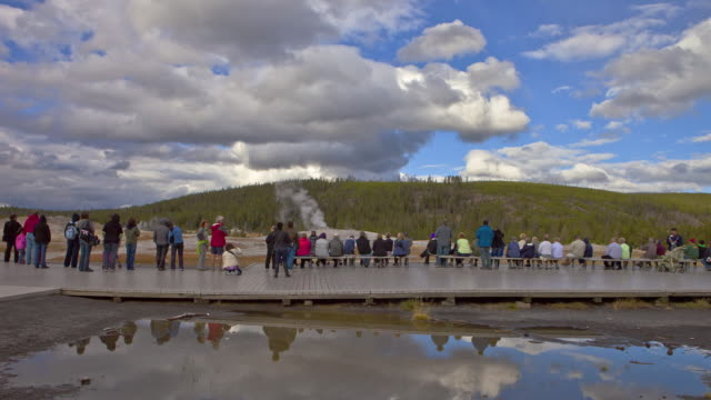 tourists gather around  the old faithful geyser  in yellowstone national park. - old faithful stock videos & royalty-free footage