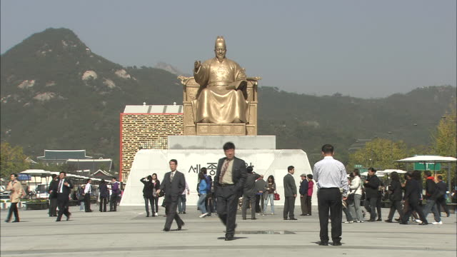 Tourists gather near a statue of Sejong the Great in Seoul.