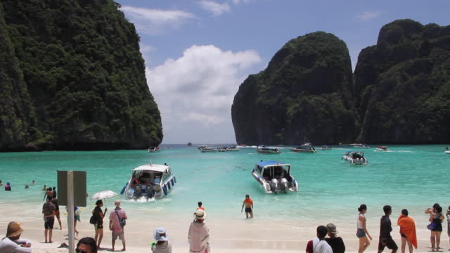 tourists gather on the beach at maya bay on ko phi phi island in southern thailand maya beach was made popular by the movie the beach - inselgruppe phi phi stock-videos und b-roll-filmmaterial