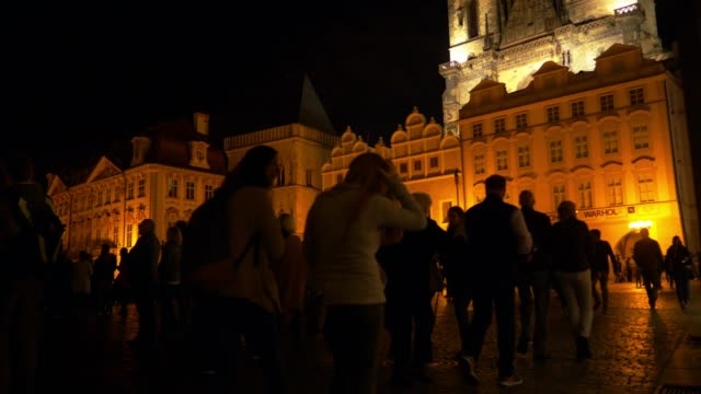 tourists gathering in prague old town square at night - prague old town square stock videos & royalty-free footage