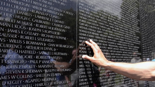 MS Tourists hand looking hero names of war dead at vietnam veterans memorial wall monument / Washington DC, Washington District of Columbia, United States
