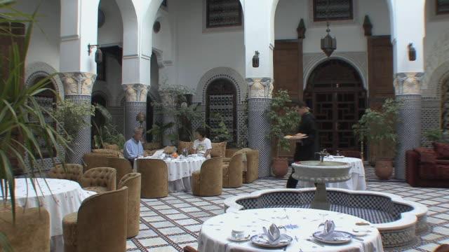 vídeos y material grabado en eventos de stock de ws tourists having breakfast in riad, fez, morocco - palacio interior