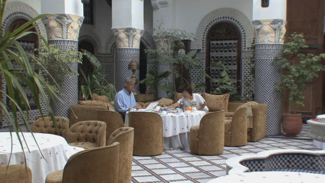 vídeos de stock, filmes e b-roll de ws tourists having breakfast in riad, fez, morocco - 65 69 anos