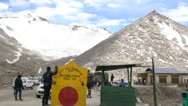 tourists having fun around the yellow sign board and prayer flags at the chang la pass, ladakh, india - anleitung konzepte stock-videos und b-roll-filmmaterial