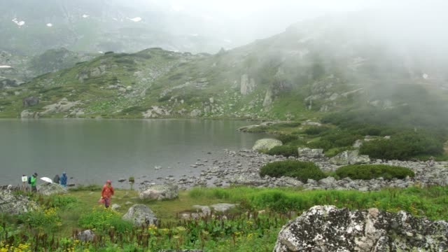 tourists hiking among the seven rila lakes in rila national park in a rainy and foggy day - bulgaria video stock e b–roll