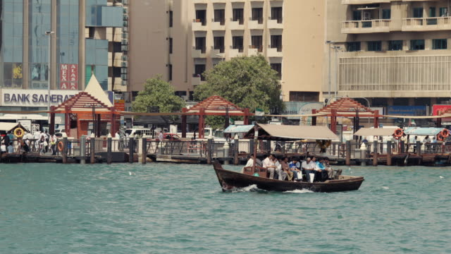 vídeos de stock e filmes b-roll de t/l ws pan tourists in boat on dubai creek / dubai, united arab emirates - barco de turismo