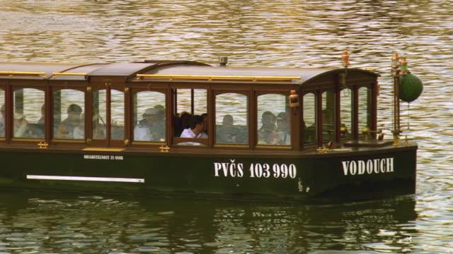 ws tourists in boat on vltava river / prague, czech republic - river vltava stock videos & royalty-free footage