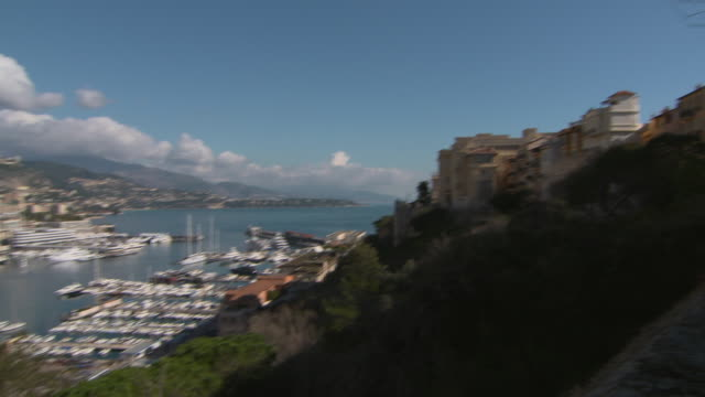 tourists in city overlooking at famous port hercules in sea against sky - monte carlo, monaco - monte carlo stock-videos und b-roll-filmmaterial
