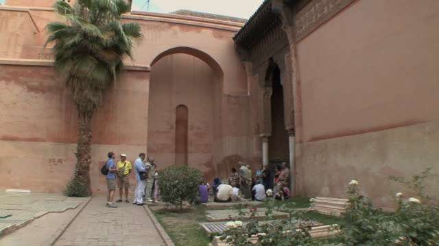 ms pan tourists in courtyard of mausoleum with saadian tombs, marrakech, morocco - 墓石点の映像素材/bロール