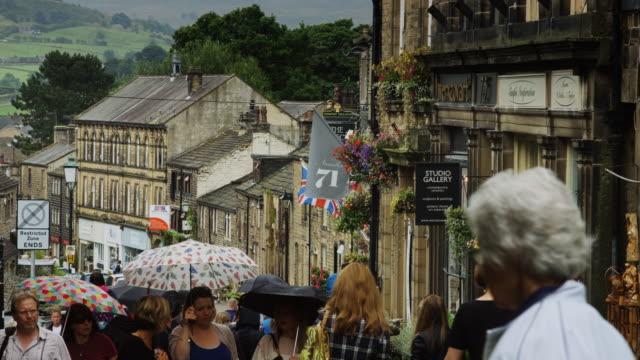 vídeos y material grabado en eventos de stock de tourists in england with umbrellas - yorkshire