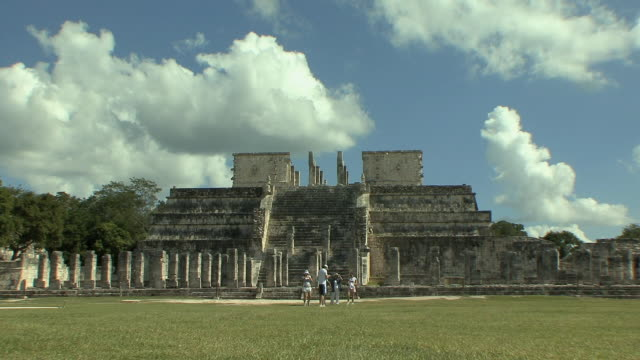 ws tourists in esplanade in front of temple of the warriors at pre-columbian archaeological site built by maya civilization / chichen itza, yucatan, mexico - colonna architettonica video stock e b–roll
