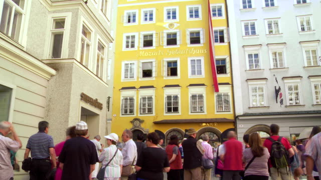 pan tl tourists in front of the birthplace of wolfgang amadeus mozart in salzburg - traditionally austrian stock videos and b-roll footage