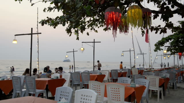 Tourists in Open air restaurant at beach in the evening