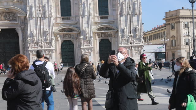 tourists in piazza duomo in milan walk and visit the city with the mask against the corona virus on the face in milan italy on february 24 2020 more... - piazza video stock e b–roll
