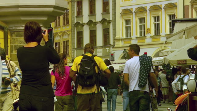 ms tu tourists in plaza, woman taking picture of yellow building / prague, czech republic - czech republic stock videos & royalty-free footage