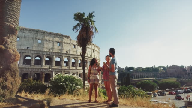 tourists in rome together by the coliseum - gente comune video stock e b–roll